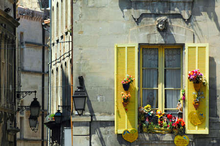 clr: Arles (Bouches-du-Rhone, Provence-Alpes-Cote dAzur, France) - Old typical buildings near the Roman Arena. Window with yellow shutters and flowers Stock Photo