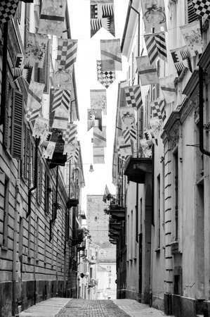 palio: Asti (Piedmont, Italy): historic street with flags for the medieval Palio. Black and white Stock Photo