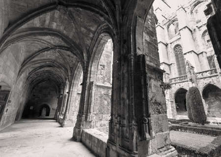 cloister: Narbonne (Aude, Languedoc-Roussillon, France), cloister of the medieval cathedral, in gothic style. Black and white Stock Photo