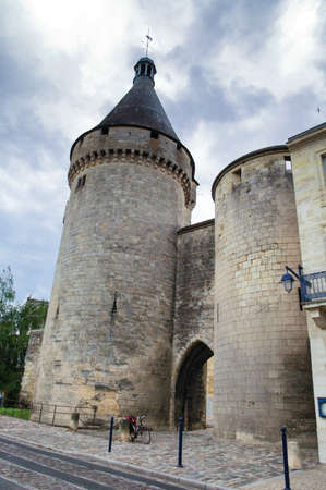gironde: Libourne (Bordeaux, Gironde, Aquitaine, France): a bicycle with red bags and a gothic tower