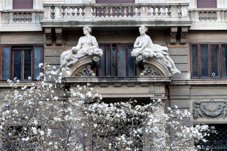 Milan (Lombardy, Italy), facade of a historic palace in Eleonora Duse square with two statues