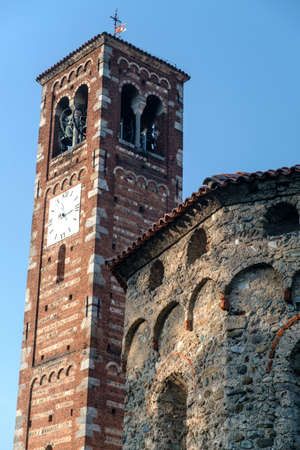 Agliate Brianza (Monza, Lombardy, Italy): exterior of the medieval church of Saints Peter and Paul, built from the 11th century: baptistery and belfry
