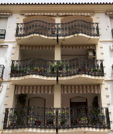 verandas: Ronda (Andalucia, Spain): facade of old typical residential building with balconies, verandas and potted plants and flowers Stock Photo