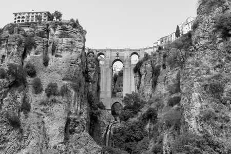 Ronda (Andalucia, Spain): view of the historic city over the canyon, the famous bridge. Black and white