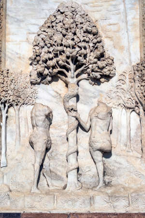 Facade of the historic Certosa di Pavia (Lombardy, Italy), medieval monument. Bas-relief: Adam and Eve