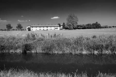 Naviglio of Bereguardo, bicycle lane from Abbiategrasso (Milan) to Bereguardo (Pavia, Lombardy, Italy) in the springtime, Old typical farm. Black and white