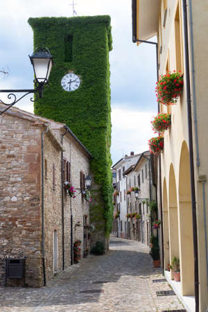 typical: Frontino, historic village in Montefeltro, Pesaro Urbino, Marches, Italy). A street with the typical houses, with plants and flowers