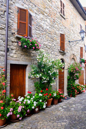 Frontino, historic village in Montefeltro, Pesaro Urbino, Marches, Italy). A street with the typical houses, with plants and flowers