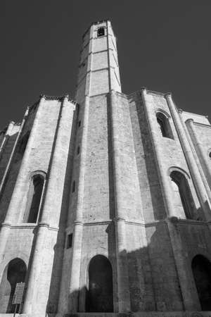 Ascoli Piceno (Marches, Italy): the famous Piazza del Popolo, the medieval main square of the city at morning. Apse of San Francesco church. Black and white Stock Photo