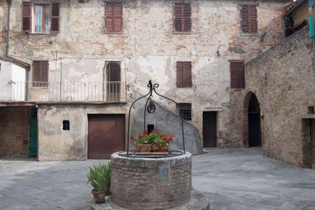Asciano, Siena, Tuscany, Italy: the old city at morning. Courtyard of typical old house with well, plants and flowers