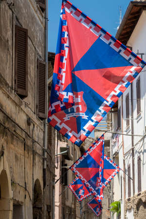 Cori, Latina, Lazio, Italy: typical street of the historic town with red and blue flags
