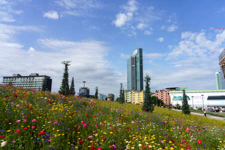 Palazzo Lombardia modern tower in Milan, Lombardy, Italy, seen from the park known as Biblioteca degli Alberi at springtime with flowers