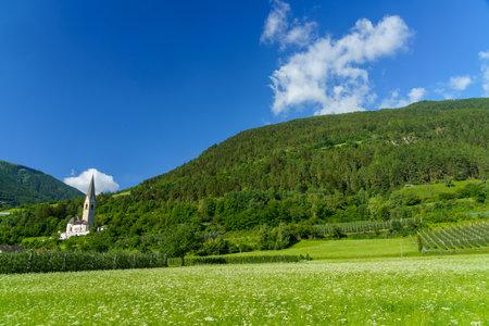 Mountain landscape along the road from Glorenza to Prato allo Stelvio, Bolzano province, Trentino Alto Adige, Italy, in the summertime. Church and orchards Archivio Fotografico