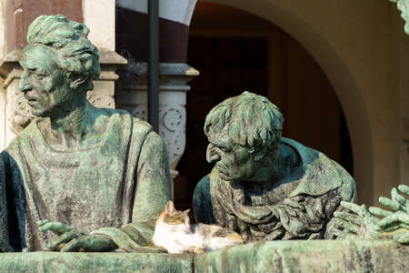 Milan, Lombardy, Italy: historic cemetery known as Cimitero Monumentale: a tomb with statues and a cat