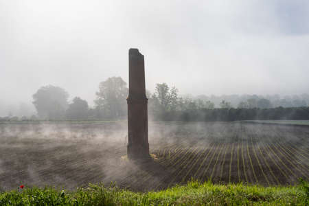 Foggy rural landscape near ruined column in a field near Asti, Piedmont, Italy, in a morning of May