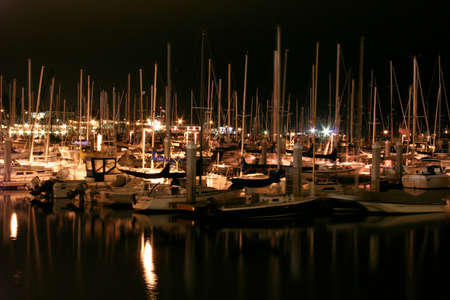 monterey: boats in a harbor at night reflecting off of the water in monterey california