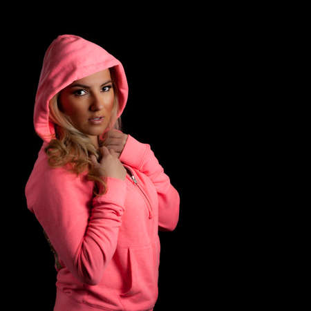 sweats: A blonde Latina girl in a pink hoodie isolated on a black background with her hands in pockets. Stock Photo