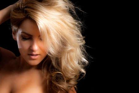 Un primer plano de un modelo de moda bonita, rubia con el pelo largo. Mano está en la cabeza. Aislado sobre fondo negro. Foto de archivo