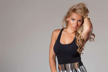 latina female: Blonde latina female fashion model with hand on hair and tan background.