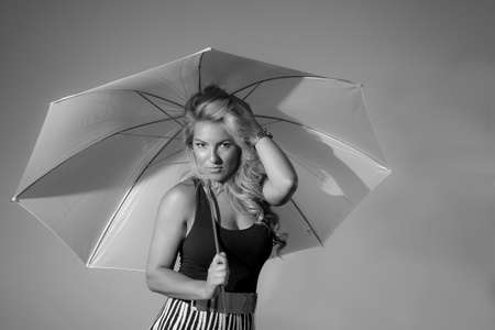 slicker: A blonde Latina model in black & white holding an umbrella.
