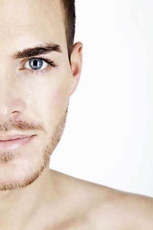 ojos azules: Retrato de un hombre joven y deportivo aislado en mitad de la cara blanca