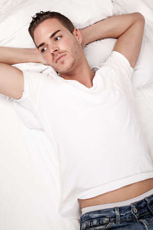 beautiful young man lying in bed Stock Photo - 19564331
