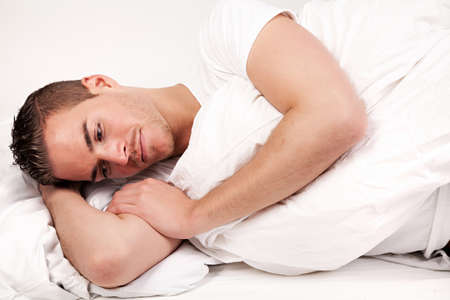 beautiful young man lying in bed photo