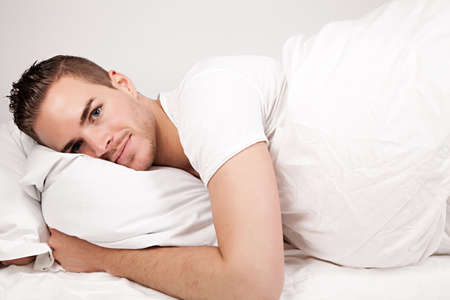 soporific: beautiful young man lying in bed Stock Photo