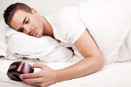 beautiful young man lying in bed looking at clock photo