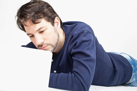 happier: young man working on laptop while laying on the floor