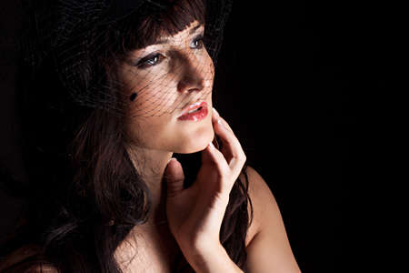 Beautiful young woman in black hat with net photo
