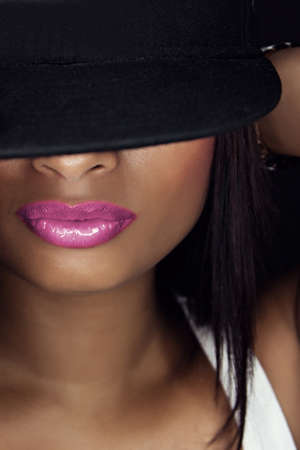 Close-up darkskin beauty with pink lipstick and cap