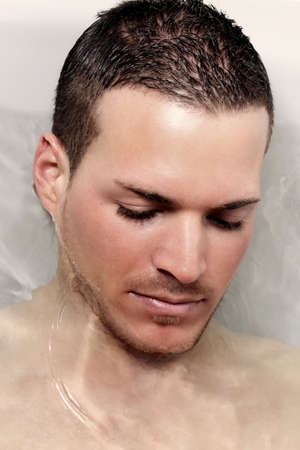 Portrait of a bautiful young man taking a bath photo