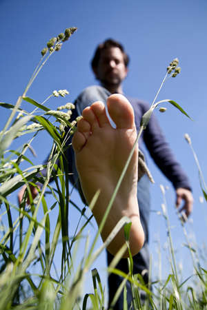 young man bare feet on green grass photo