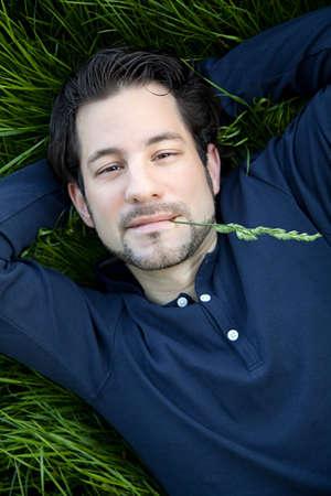 beautiful young man lying on green gras Stock Photo - 20048114