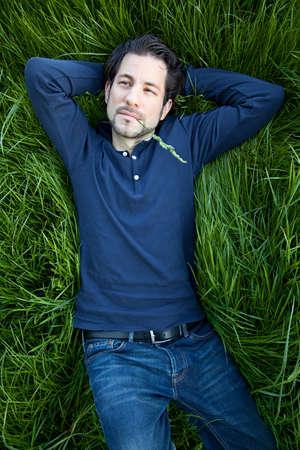 beautiful young man lying on green gras photo