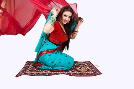 Beautiful young indian woman in traditional clothing sitting on a flying carpet, isolated on white photo