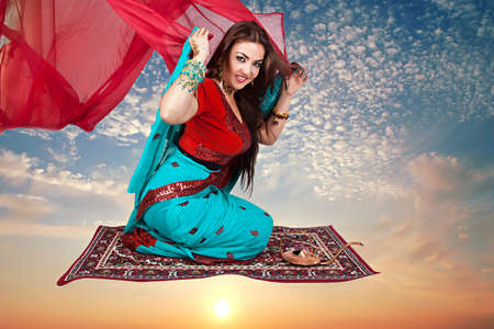 Beautiful young indian woman in traditional clothing sitting on a flying carpet photo
