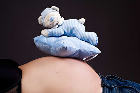 baby music box on pregnant belly Stock Photo
