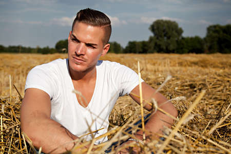 Portrait of  a beautiful young man outdoors in white casual shirt sitting on hay field photo