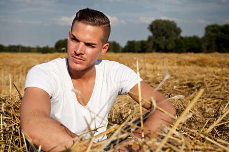 hay field: Ritratto di un uomo giovane e bella all'aperto in camicia casual bianco seduto sul campo di fieno
