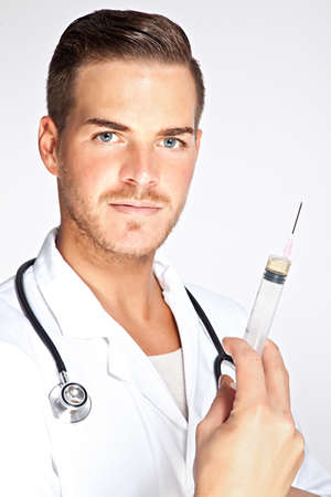 Portrait of young male doctor holding syringe with injection Stock Photo