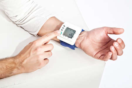 diastolic: Photo of young man's hand measuring his blood pressure