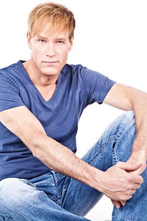 Portrait attractive middelaged man sitting against white background