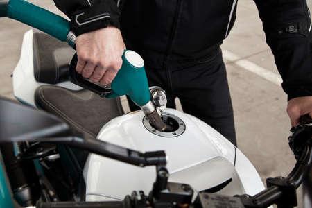 l petrol: boquilla de combustible en la mano vertiendo a la motocicleta en la estaci�n de gas