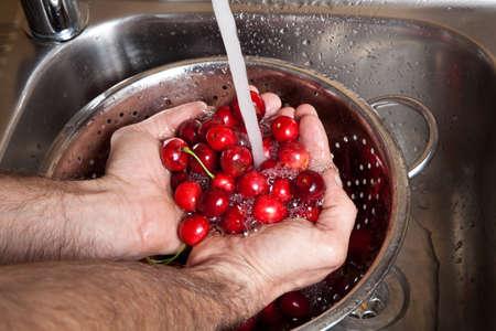 male hands wash cherries under running water in kitchen