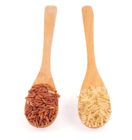 Red rice and brown rice in wooden spoon isolated on white background photo