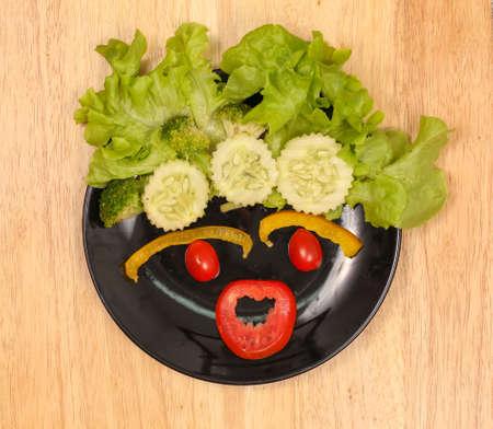 fondo legno: Verdure sul piatto nero su sfondo di legno