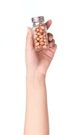 monkey nut: hand holding bottle of peanuts isolated on white background