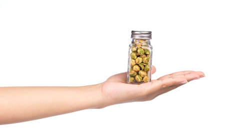 hand holding bottle: hand holding bottle of roasted Green beans snacks coated by flour and spicy isolated on white background